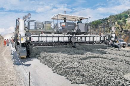 Avec des pavés de glissement plus larges, la charrue d'étalement distribue le béton sur toute la largeur de travail.