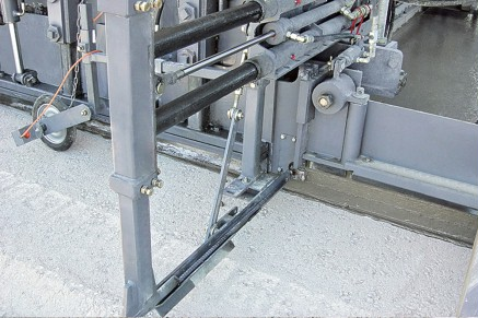 The side tie bar inserter drives tie bars laterally into the concrete slab
