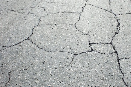 The surface course must be rehabilitated due to severe cracks in the roadway.