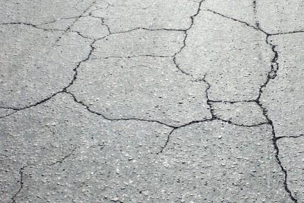 La couche de surface doit être réhabilitée en raison de fissures sévères dans la chaussée.