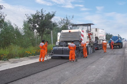 Paving a hydraulically bound base layer. Precisely metered quantities of cement slurry are added via hose connections from the slurry mixer to the cold recycler.